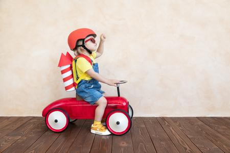 Capretto con razzo di carta giocattolo. Bambino che gioca in casa. Concetto di tecnologia di successo, immaginazione e innovazione Archivio Fotografico