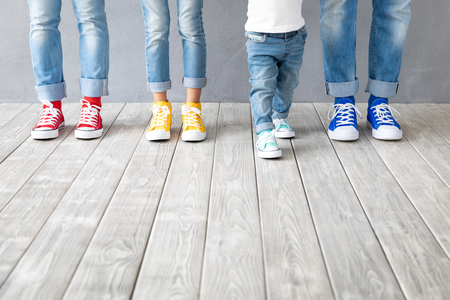 Peoples feet in colorful sneakers. Happy family - father, mother, son and daughter indoor. Parents and children at home