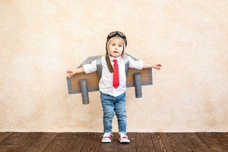 Funny kid with toy jet pack. Happy child playing at home. Success, imagination and innovation technology concept 免版税图像