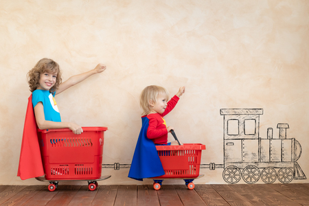 Bambini felici che giocano in casa. Bambini divertenti che guidano una macchinina al coperto. Successo e concetto di vittoria