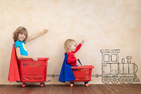 Szczęśliwe dzieci bawiące się w domu. Śmieszne dzieci jazdy autko kryty. Koncepcja sukcesu i wygranej