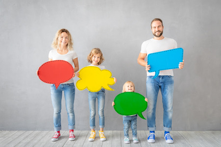 Happy family - father, mother, daughter and son - holding colorful paper speech bubble blank. People with two kids having fun indoor.