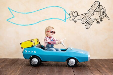 Happy child playing at home. Funny kid driving toy car indoor. Vacation and travel concept