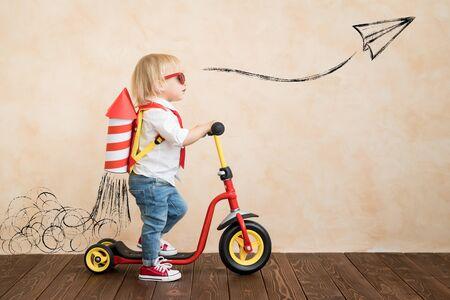 Bambino felice che gioca con il razzo giocattolo a casa. Ragazzino divertente che guida scooter. Successo e concetto di vittoria Archivio Fotografico