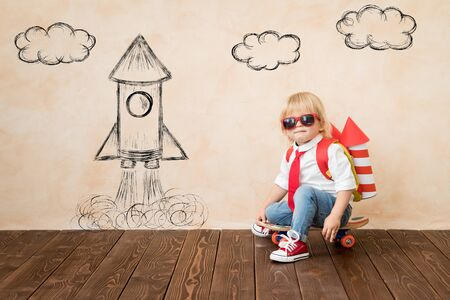Lustiges Kind mit Spielzeug-Jet-Pack. Glückliches Kind, das zu Hause spielt. Erfolgs-, Vorstellungs- und Innovationstechnologiekonzept Standard-Bild