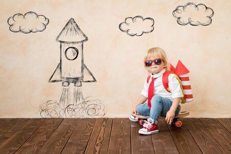 Niño divertido con jet pack de juguete. Niño feliz jugando en casa. Concepto de tecnología de éxito, imaginación e innovación. Foto de archivo