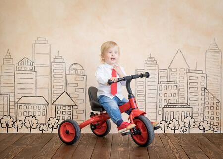 Happy child pretend to be businessmen. Funny kid playing at home. Education, start up and business idea concept Standard-Bild