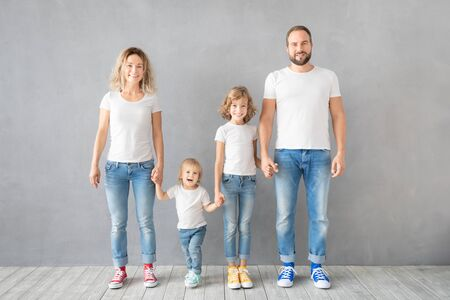 Happy family standing against grey background. Parents with children having fun at home. Portrait of father, mother, daughter and son