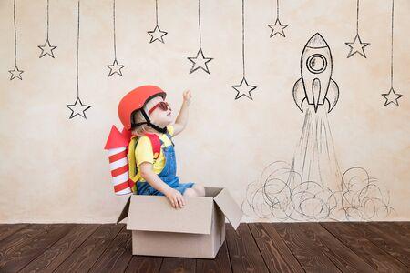 Capretto con razzo di carta giocattolo. Bambino che gioca in casa. Concetto di tecnologia di successo, immaginazione e innovazione
