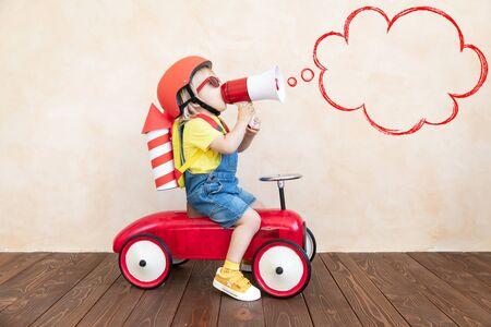 Niño con cohete de papel de juguete. Niño jugando en casa. Concepto de tecnología de éxito, imaginación e innovación. Foto de archivo