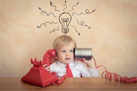 Gelukkig kind doet zich voor als zakenlieden. Grappige jongen die thuis speelt. Onderwijs, opstarten en business idee concept