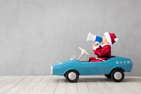 Happy child dressed Santa Claus costume playing at home. Funny kid driving toy car and speaking by megaphone. Christmas holiday concept Stock Photo