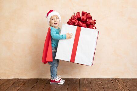 Glückliches Kind gekleideter Superheld, der Weihnachtsgeschenkbox hält. Lustiges Kind im Superheldenkostüm mit Weihnachtsgeschenk
