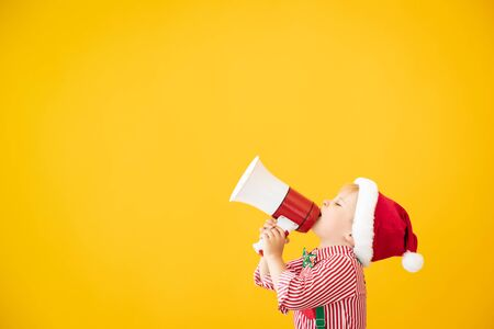 Happy child wearing Santa Claus costume speaking by megaphone. Portrait of funny kid against yellow background
