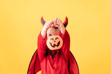 Funny child dressed devil costume against yellow background. Happy Halloween holidays concept 免版税图像