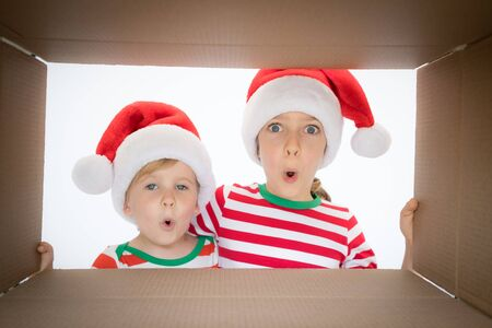 Happy children looking into the box. Funny surprised kids unpack Christmas gift box. Xmas holiday concept. Low angle view.