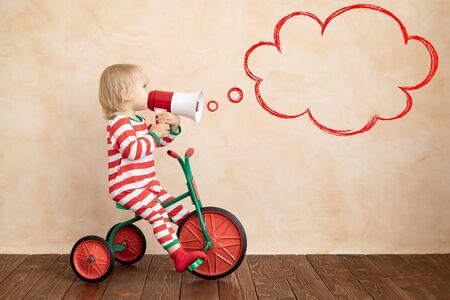 Bambino felice vestito costume di Babbo Natale che gioca in casa. Bambino divertente che guida una macchinina e parla al megafono. Concetto di vacanza di Natale