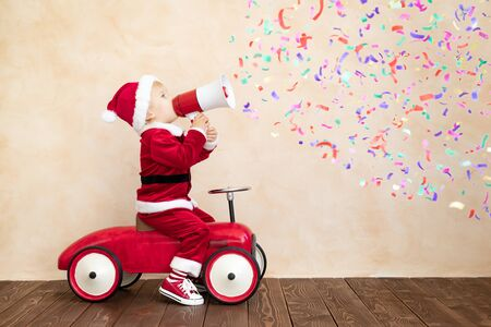Happy child dressed Santa costume playing at home. Funny kid driving toy car and speaking by megaphone. Christmas holiday concept