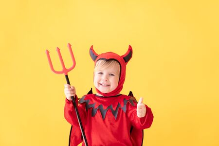 Funny child dressed devil costume showing thumbs up against yellow background. Happy Halloween holidays concept