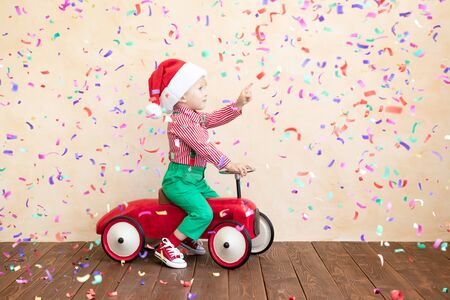 Happy child wearing Santa Claus costume playing at home. Funny kid driving the toy car against falling confetti background. Christmas holidays concept