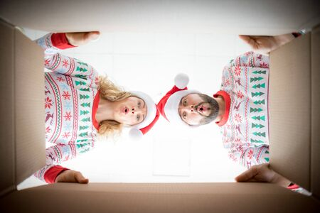 Happy woman and man looking into the box. Funny surprised couple unpack Christmas gift box. Xmas holiday concept. Low angle view.