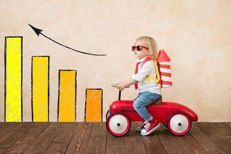 Bambino felice che gioca con il razzo giocattolo a casa. Bambino divertente che guida l'automobile del giocattolo dell'interno. Successo e concetto di vittoria