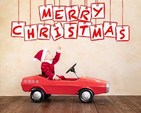 Happy child wearing Santa Claus costume playing at home. Funny kid driving the toy car. Christmas holidays concept