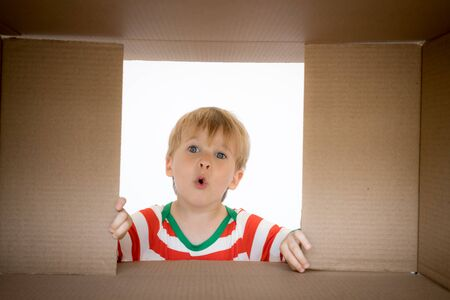 Happy child looking into the box. Funny surprised baby boy unpack Christmas gift box. Xmas holiday concept. Low angle view.