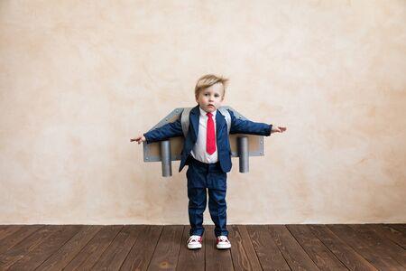 Portret van jonge zakenman met speelgoed papieren vleugels. Gelukkig kind dat thuis speelt. Kind plezier. Succes, creatief en start-up concept Stockfoto