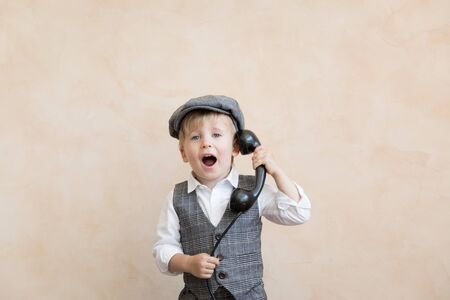 Happy child pretend to be businessmen. Funny kid talking by phone. Business negotiations concept