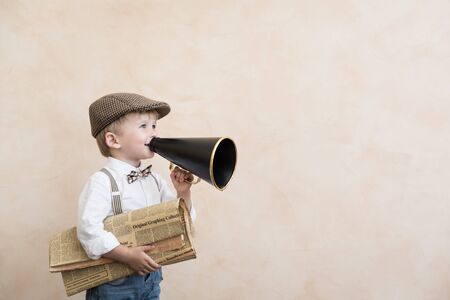 Child holding loudspeaker and newspaper. Kid shouting through vintage megaphone. Business news concept Stockfoto
