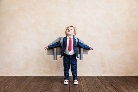 Ritratto di giovane uomo d'affari con ali di carta giocattolo. Bambino felice che gioca in casa. Ragazzo che si diverte. Successo, concetto creativo e di avvio Archivio Fotografico
