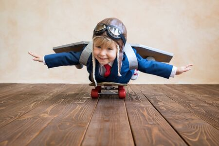 Portrait of young businessman with toy paper wings. Happy child playing at home. Kid having fun. Success, creative and start up concept Stock Photo