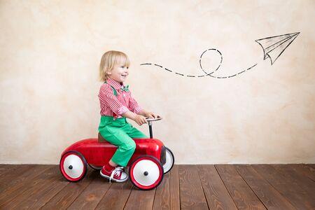 Bambino felice che guida un'auto d'epoca. Bambino che si diverte a casa. Immaginazione e concetto di infanzia