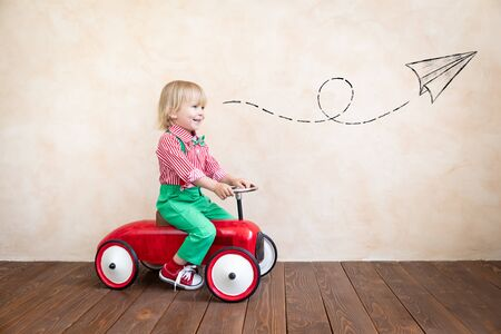 Happy child riding vintage car. Kid having fun at home. Imagination and childhood concept