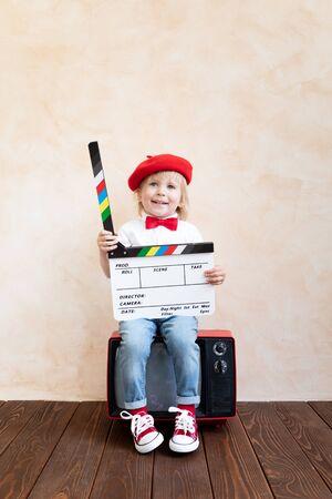 Lustiges Kind, das Klöppelbrett hält. Glückliches Kind, das Spaß zu Hause hat. Retro-Kinokonzept