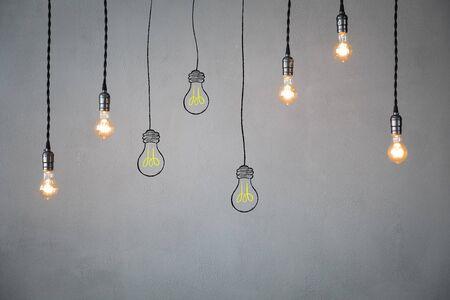 Muchas bombillas contra el fondo de la pared de hormigón. Concepto de idea Foto de archivo