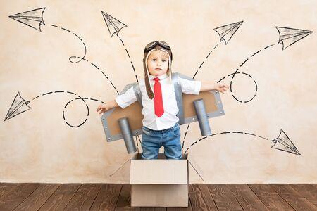 Niño divertido con jet pack de juguete. Niño feliz jugando en casa. Concepto de tecnología de éxito, imaginación e innovación.
