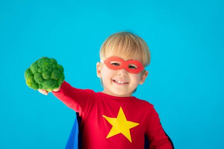 Superhero child holding broccoli. Kid pretend to be super hero. Healthy eating concept