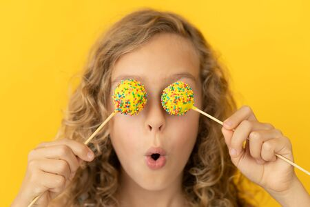 Happy child holding lollipop. Portrait of funny girl against yellow background