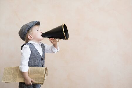Child holding loudspeaker and newspaper. Kid shouting through vintage megaphone. Business news concept 版權商用圖片
