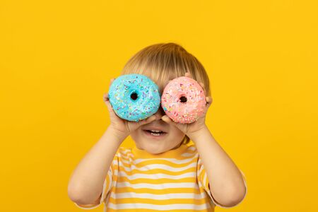 Happy child holding glazed donut. Portrait of funny kid against yellow background