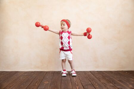 Happy child playing at home. Funny kid wants to become a sportsman. Healthy lifestyle concept
