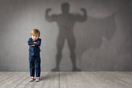 Happy child wants to become a super hero. Funny kid dreams of becoming a superhero. Imagination and motivation concept