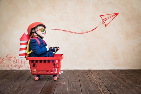 Gelukkig kind dat thuis speelt. Grappige jongen rijden op skateboard. Jeugddroom, vrijheid en winnaarconcept Stockfoto