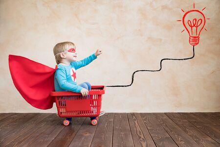Szczęśliwe dziecko bawiące się w domu. Śmieszne dziecko jazda na deskorolce. Pomysł, sukces i koncepcja zwycięzcy
