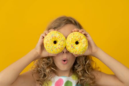 Happy child holding glazed donut. Portrait of funny girl against yellow background