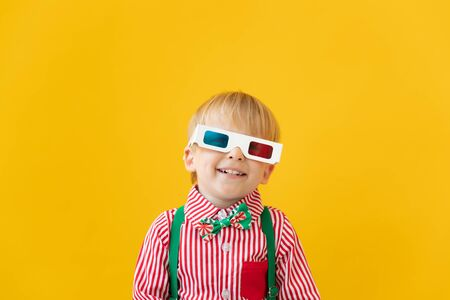 Happy child wearing 3d glasses. Surprised kid against yellow background. Cinema and movie time concept Foto de archivo - 138047474