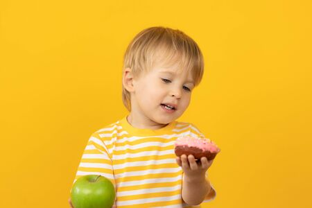 Happy child holding donut and apple. Portrait of funny kid against yellow background. Healthy food concept. Difficult choice Foto de archivo - 138047478