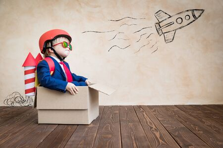 Happy child playing at home. Funny kid sitting in cardboard box. Childhood dream, freedom and winner concept